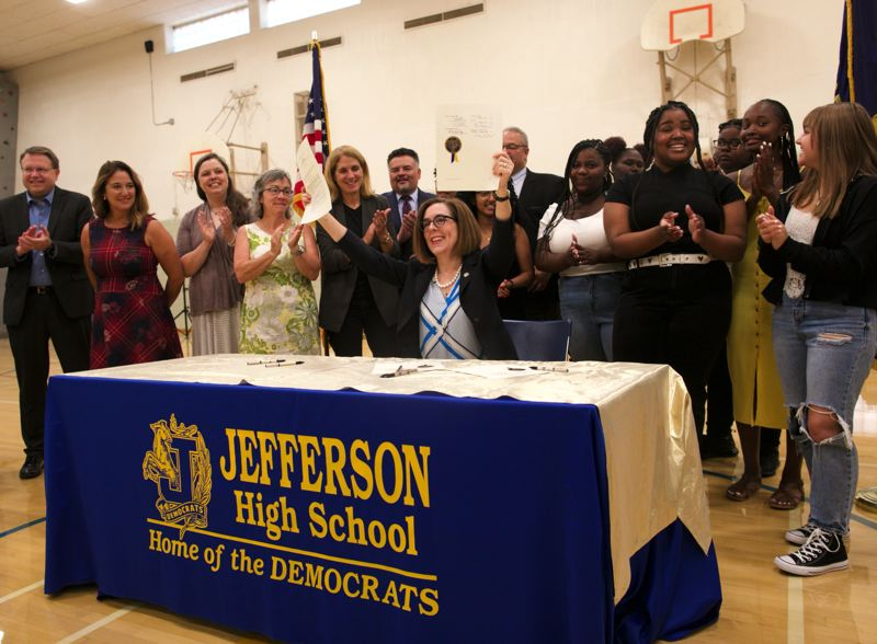 PMG PHOTO: JAIME VALDEZ - Oregon's Student Success Act, signed Wednesday morning, Aug. 28, by Gov. Kate Brown, provides $2 billion more for schools. Brown was surrounded by Jefferson High School freshmen when she ceremonially signed the act.