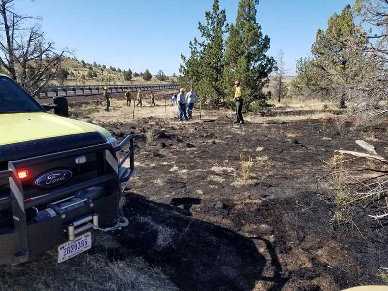 SUBMITTED PHOTO - Firefighters ensure that a wildfire, started by a semitruck brake part, is dead out north of Madras, along U.S. Highway 97. A deputy was first at the scene and knocked down the flames before firefighters arrived.