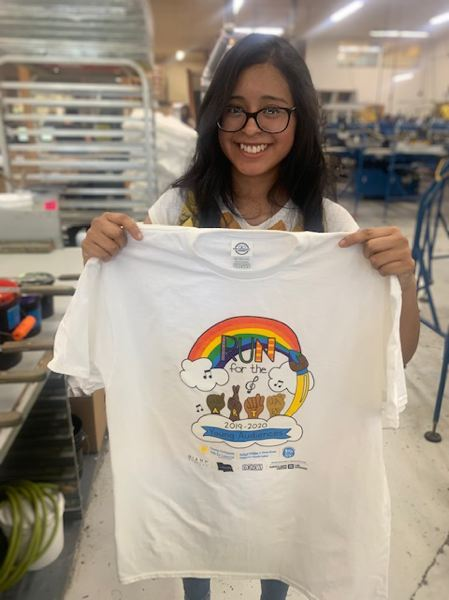 COURTESY PHOTO - Grace Brown, a Scappoose student, holds up a freshly made T-shirt featuring a design she co-created with classmate Raleigh Erickson for a contest by Run for the Arts, an educational nonprofit, earlier this year.
