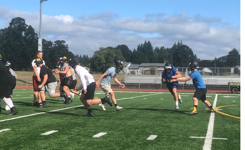 PMG PHOTO: STEVE BRANDON - During practice last week, quarterback Jakob Robbins hands off to Austin Waite, as defender Ashton Smith looks to cut off the play and Maverick Rask (white shirt) sets up to block.