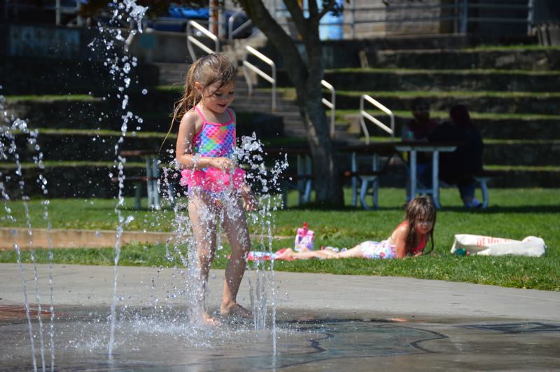 PMG PHOTO: NICOLE THILL-PACHECO - Riley Eubanks, 3, dances through a spray of water at the splash pad in Columbia View Park in St. Helens, on Tuesday, Aug. 27, while her sister, MacKenzie Eubanks, 5, lounges on a towel in the background. The two girls visited the park with their grandma, Lori Randolph, on Tuesday as a way to cool off amidst a two-day heat wave. For more on the heat wave, see A7.