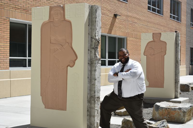 PMG PHOTO: TERESA CARSON - Drake Shelton, Gresham High Schools new principal, stands among the beautifully restored bas relief muse sculptures in the new schools muse courtyard. The sculptures were carefully removed from the entrance to the old high schools theatre.
