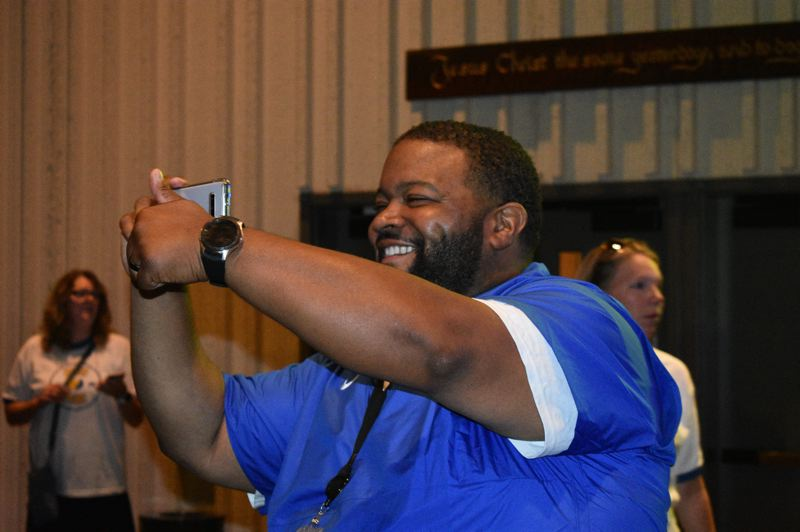 PMG PHOTO: TERESA CARSON - Drake Shelton takes a video Wednesday, Aug. 28 at the Gresham-Barlow School Districts convocation, which is a spirited pep rally welcoming staff to the school year.