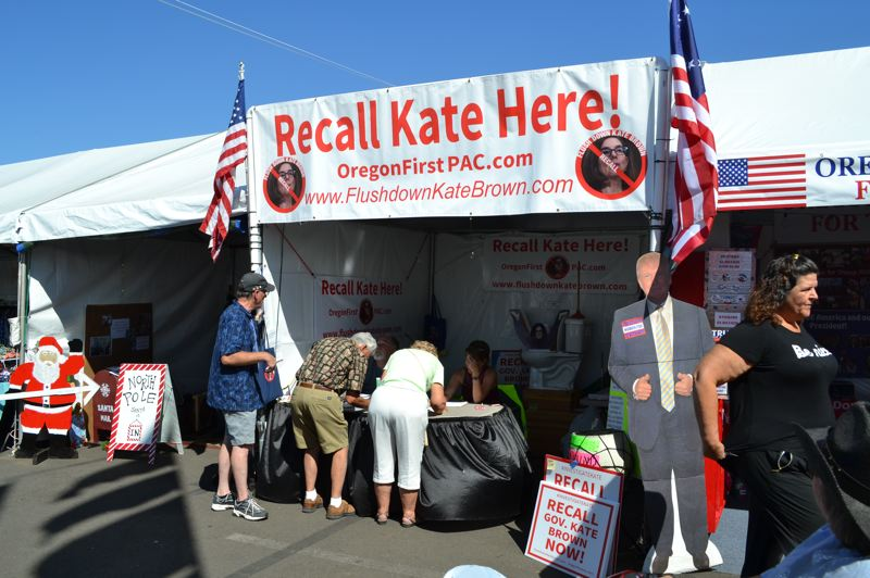 OREGON CAPITAL BUREAU: CLAIRE WITHYCOMBE - Oregon State Fair visitors sign a petition to recall Gov. Kate Brown at the booth organized by Flush Down Kate Brown.