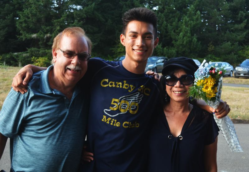 PMG PHOTO: DEREK WILEY - Canby senior Matthew Powell, with his parents, was honored Thursday before the Canby Invitational at Molalla River State Park.