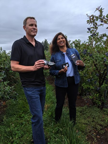 PAMPLIN MEDIA GROUP: JAIME VALDEZ - ON THE COVER: Curry & Co Farms president Aaron Ensign, and Ninette Vaz, Intel Global Supply Chain IoT Senior Manager, hold hubs and sensors that stick to flats of fruit and give near real time data about the state of the crop from picking to retail.