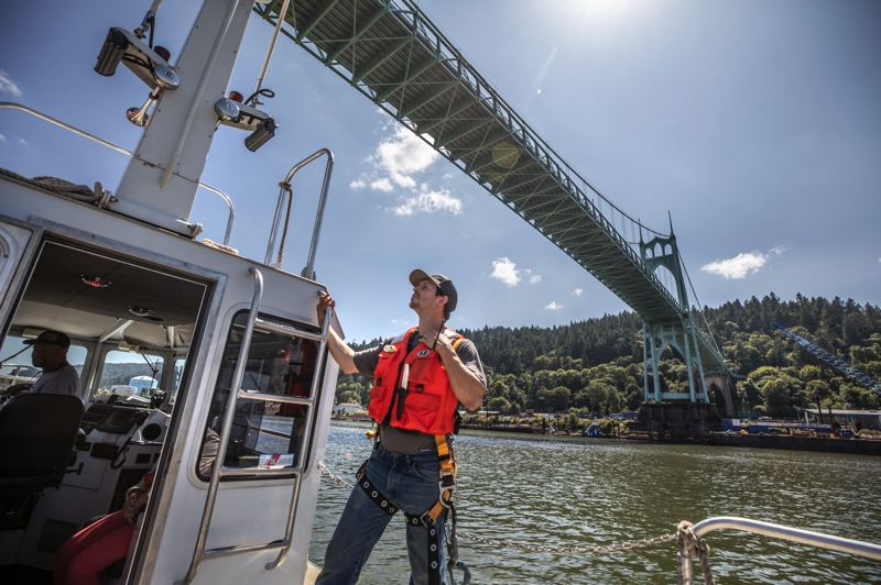 PMG PHOTO: JONATHAN HOUSE - A crewmember surveys the water near the St. Johns Bridge, which could face increased congestion as new apartment blocks spring up in the far-north Portland neighborhood.