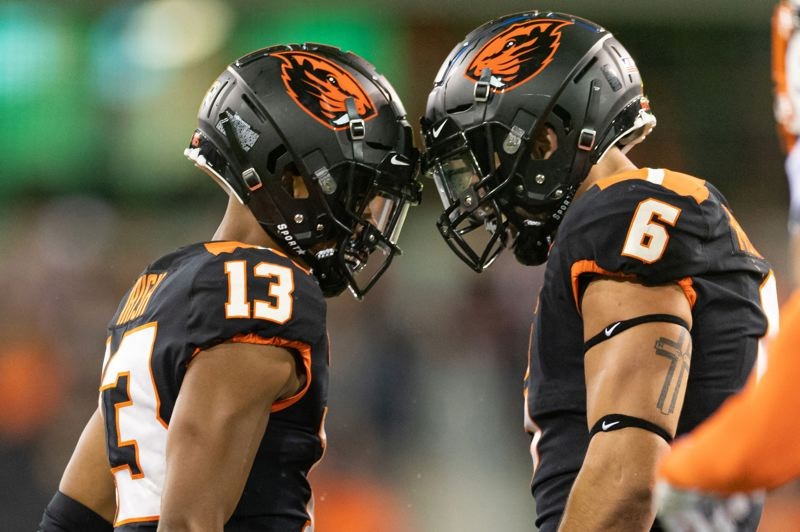 PMG PHOTO: CHRISTOPHER OERTELL - Oregon State receiver Jesiah Irish (left) and Beavers quarterback Jake Luton put their heads together during Friday night's season opener at Reser Stadium. Oklahoma State defeated OSU 52-36.
