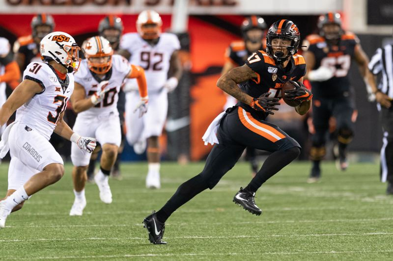 PMG PHOTO: CHRISTOPHER OERTELL - Oregon State wide receiver Isaiah Hodgins (right) eludes the Oklahoma State defense after a reception during the Friday night season opener for both teams at Reser Stadium.