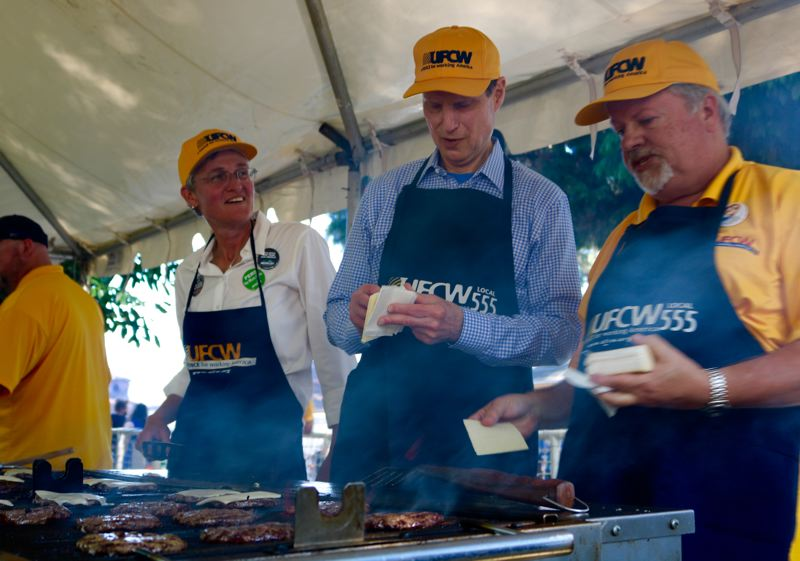 PMG PHOTO: ZANE SPARLING - U.S. Sen. Ron Wyden slapped cheese on burgers during the 2019 Labor Day celebration, later telling the crowd he thought 'every day ought to be Labor Day.'