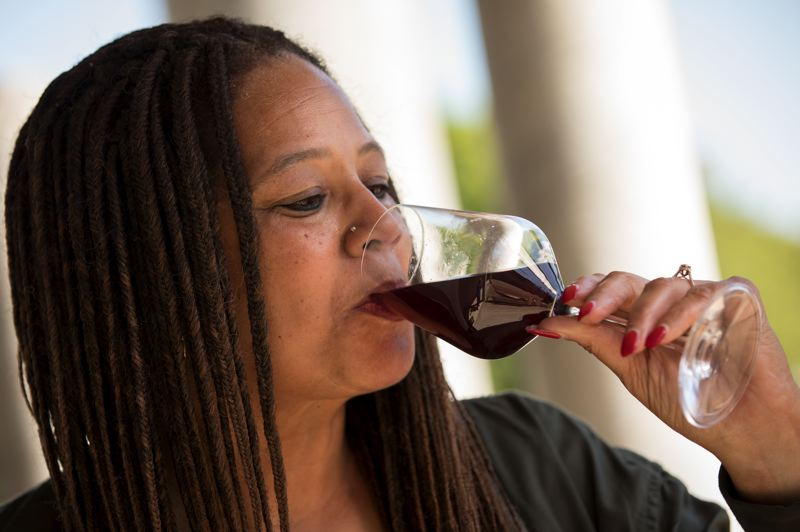 PMG PHOTO: JAIME VALDEZ - Donna Stoney, pictured sampling a glass of red wine, is recognized as the first black woman winemaker in Oregon. She began learning the art of winemaking from Bertony Faustin, owner of Abbey Creek Vineyards in North Plains.