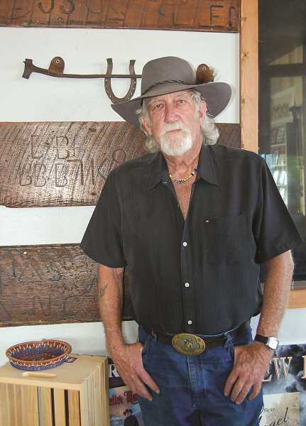 RAMONA MCCALLISTER - Rick Steber stands in front of the planks taken from the building that date back to when it was a blacksmith business. The planks still have the branding marks on them, and one of the original branding irons was also found during the renovation.  ABOVE LEFT: Ben Northcutt stands by his first saddle, which is on display in the showroom at Rick Steber & Company-Makers.
