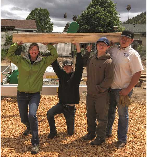 PHOTO COURTESY OF CROOK COUNTY SCHOOL DISTRICT  - Natural Resource teacher, Lisa Keown, and students from left, Keaton Brown, Nathan Rivers and Ian Stewart show their first piece of dimensional lumber milled from their new Lucas Mill.