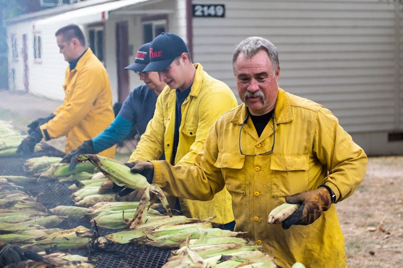 PMG PHOTO: CHRISTOPHER OERTELL - Forest Grove Fire Chief Michael Kincade and his firefighters tend to corn on the grill during last year's Corn Roast in downtown Forest Grove.