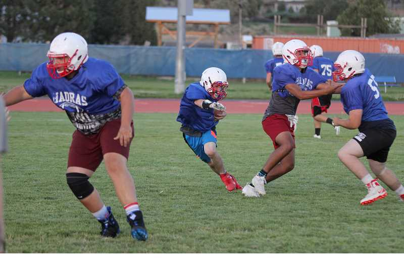 STEELE HAUGEN - Dalton Kiefer uses his blockers to create more running space during a drill.
