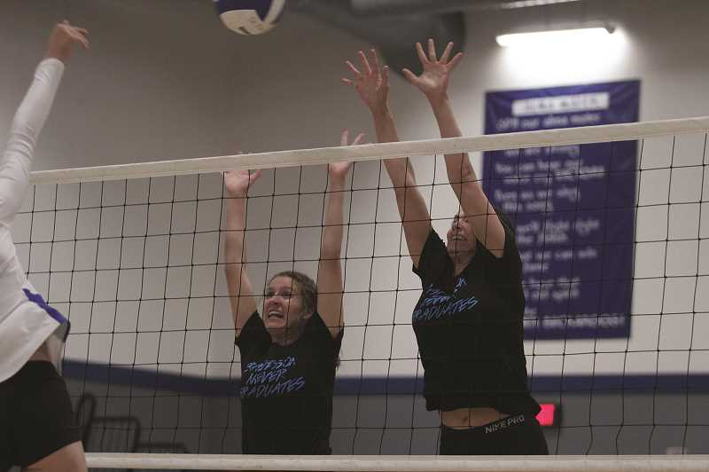 PMG PHOTO: PHIL HAWKINS - St. Paul 2019 graduate Sadie Smith (left) and 2009 graduate Julie Drescher (right) rise up to defend the net in the opening set of the Buckaroos 2019 alumni game on Thursday.