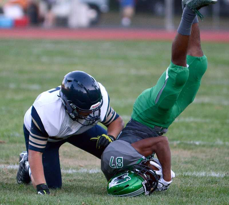PMG FILE PHOTO - Landing head-first on the turf can also rattle a players brain, which is why contact drills are limited in Oregon high school football practices.