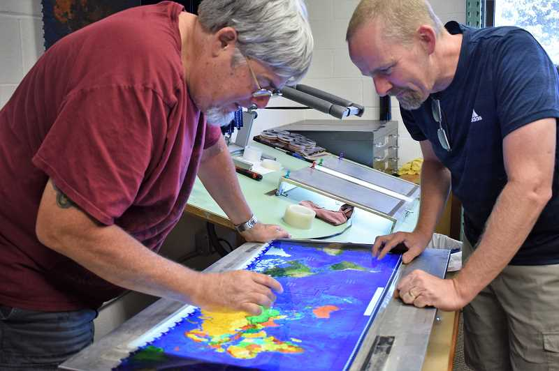 PMG PHOTO: EMILY LINDSTRAND - Members of the Geochron team study a map that will later be placed on one of the clocks.