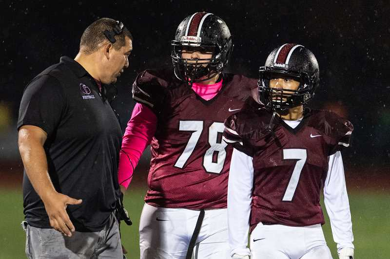 PMG PHOTO: CHRISTOPHER OERTELL - Glencoe head coach Ian Reynoso speaks to Jonathan Ashford (78) and Kainoa Stout (7) during an OSAA football game against Newberg High School last season at Hare Field in Hillsboro.
