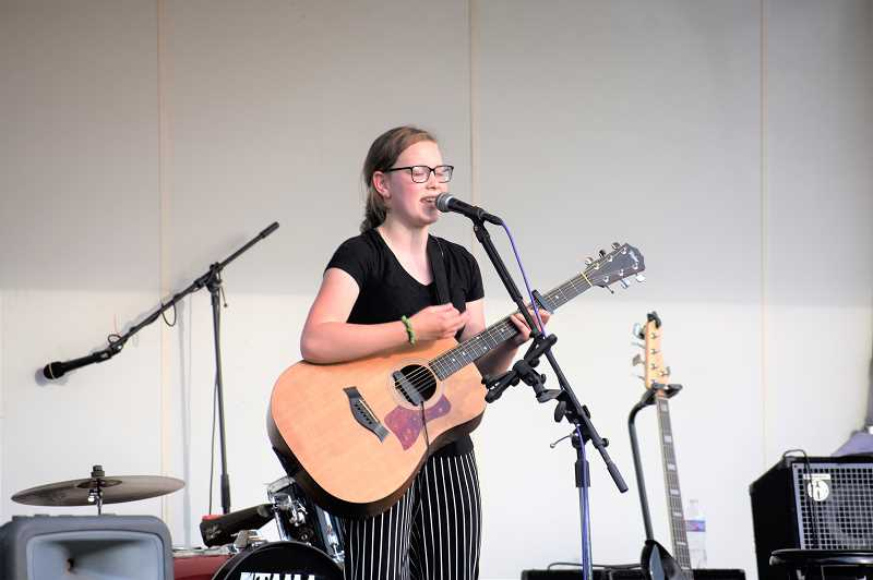PMG PHOTO: EMILY LINDSTRAND - Alaina Fidanzo, 14, sings and plays guitar during the final summer concert at Wade Creek Park on Wednesday, Aug. 28.