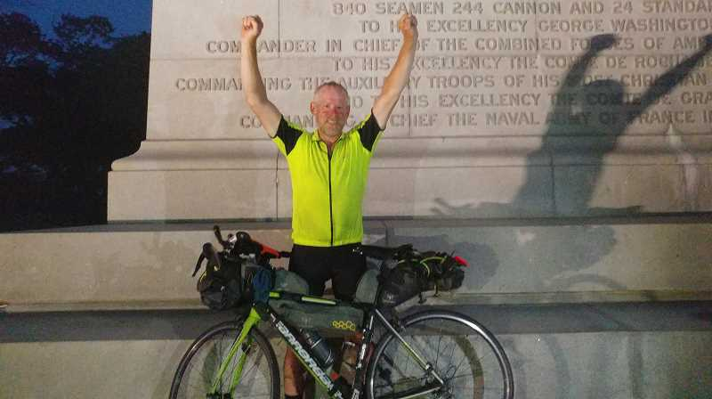 COURTESY PHOTO: VICTOR HARSHMAN - Victor Harshman is triumphant upon reaching the Victory Monument in Yorktown, Va., on Saturday, June 29, after completing the Trans Am Bike Race.