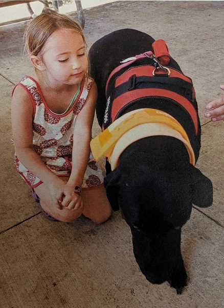 COURTESY PHOTO - A young attendee of last year's Estacada Bark for Life spends time with a furry friend.