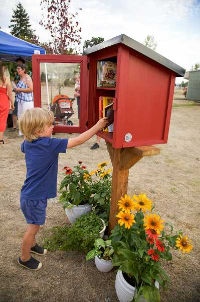 COURTESY PHOTO: KATI BODLE, CREATIVE JUICES PHOTOGRAPHY - Barbara Sandgren's great grandson August Orchard peeks at the books in the Little Free Library.