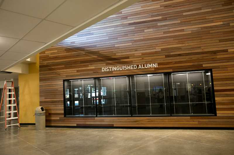 PMG PHOTO: JAIME VALDEZ - The wood paneling encasing the 'Distinguished Alumni' cabinet came from reclaimed wood taken from some of the structured demolished during renovation and construction at Tigard High School.