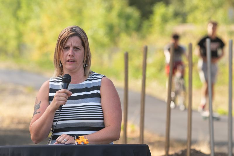 PMG PHOTO: JONATHAN HOUSE - Amanda Pietz of the Oregon Department of Transportation makes a few remarks during the groundbreaking of the Heritage Trail in Tigard, as trail users ride along the temporary asphalt pathway in the background.