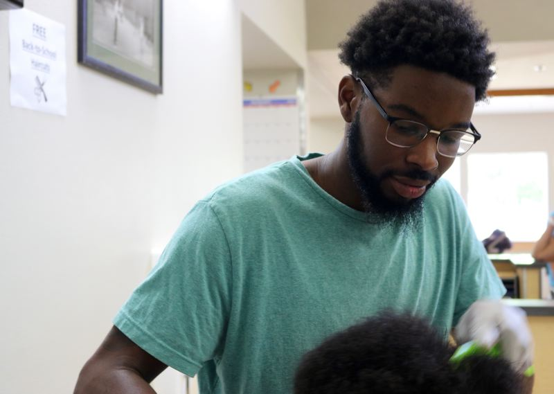 PMG PHOTO: ZANE SPARLING  - Isaiah Ford-Lucas cut kids' hair for free during a birthday celebration for Commissioner Charles Jordan on Saturday, Aug. 31 in Portland.