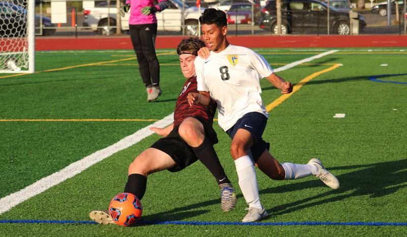 PMG PHOTO: JIM BESEDA - Gladstone defender Logan Greco (left) knocks the ball away from Stayton's Santos Navarro inside the Gladiators' 16-yard box during the first half of Tuesday's non-conference boys soccer game.
