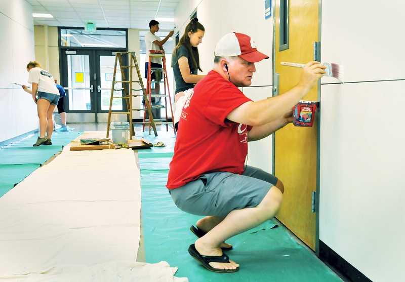 GRAPHIC PHOTO: GARY ALLEN - Justin Patterson, whose son is a junior at Newberg High School, joined about a dozen other volunteers painting the science hall at the school in August.