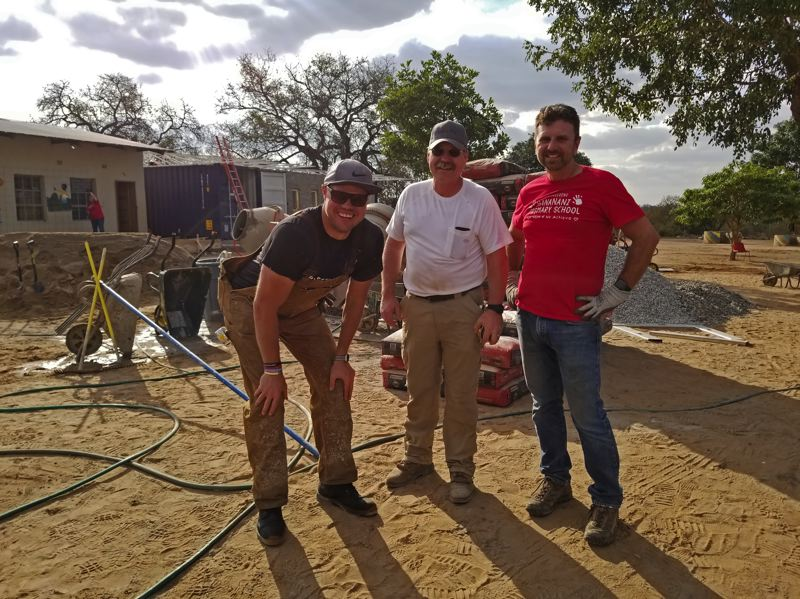 COURTESY: ANDERSEN CONSTRUCTION - (L-R) Joel Andersen, Bob Brockamp and Jack Rae, all with Andersen Construction, take a break from working on building a new shipping container classroom for students at Hananani Primary School in rural South Africa.