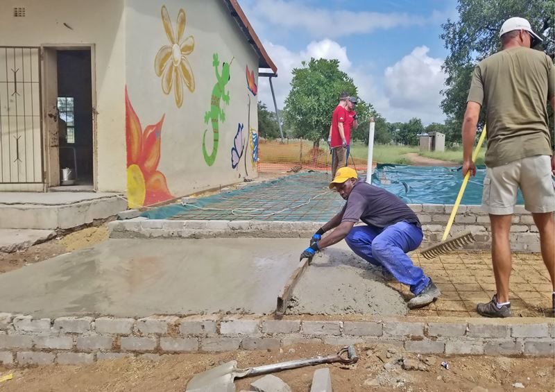 COURTESTY: ANDERSEN CONSTRUCTION - The team from Andersen Construction and its charitable division, Andersen Construction Foundation, taught villagers how to finish concrete.