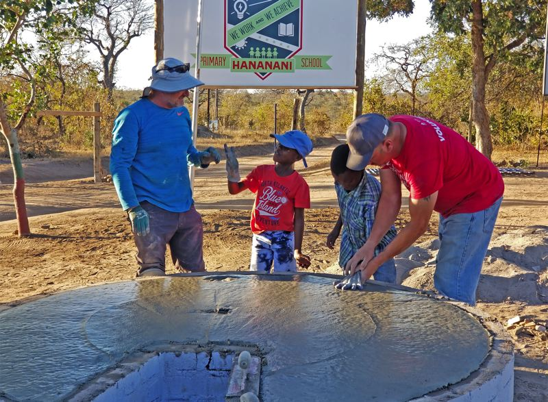 COURTESY: ANDERSEN CONSTRUCTION - Andersen's team joined with village volunteers and local kids to celebrate a final big pour by placing their handprints in freshly laid concrete.