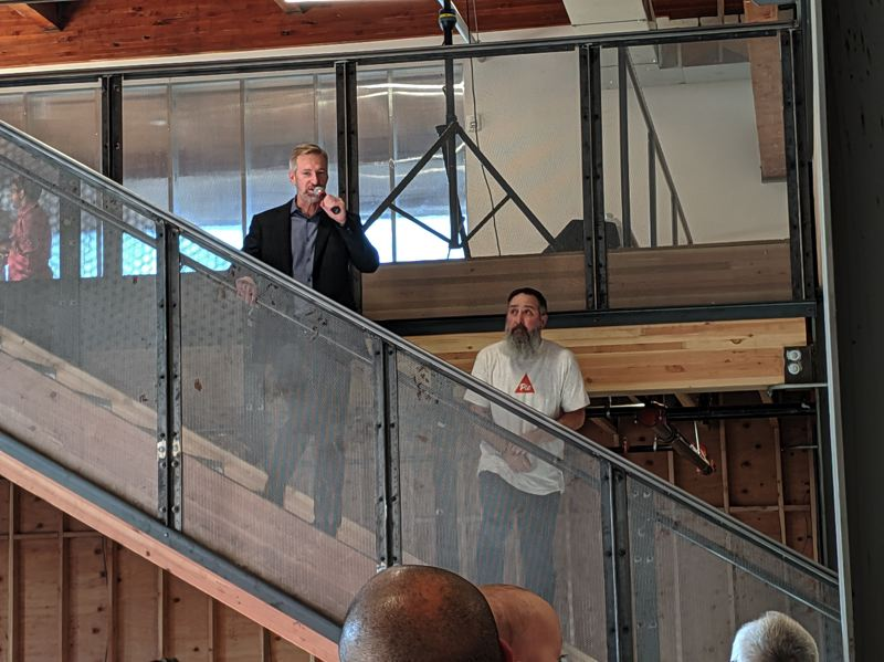 PMG PHOTO: JOSEPH GALLIVAN - At the 10th anniversary of PIE at Glass Lab, Portland Mayor Ted Wheeler (left) praises Turoczy and PIE for all they have done for the Portland startup scene and for economic development.