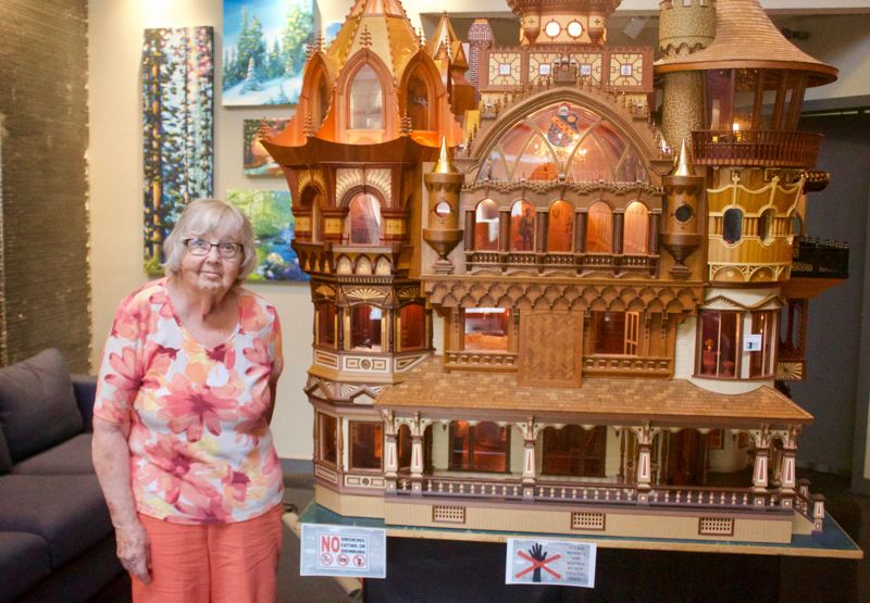 PMG PHOTO: CHRISTOPHER KEIZUR - Mary Helen Plumb stands with her late husband Bruces Mansion miniature, which is on display with many of his other pieces in Gresham.