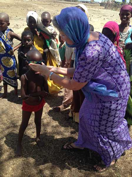 CONTRIBUTED BY KATHY VAUGHAN  - Kathy Vaughan helps Orma children try on sunglasses.