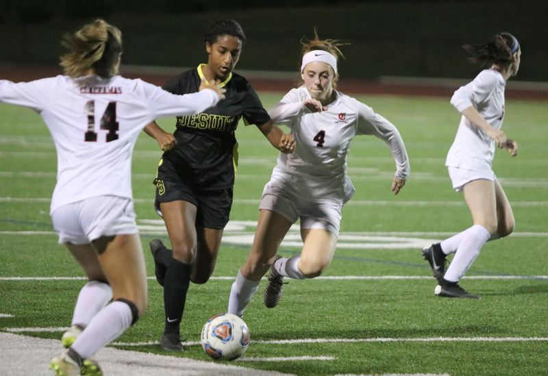 PMG PHOTO: JIM BESEDA - Clackamas' Ava Peterson (14) and Kiah Wetzell (4) converge on Jesuit's Jaiden McClellan (8) during the second half of Thursday's non-conference girls soccer game at Jesuit High School.