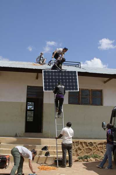 COURTESY PHOTO - Solar Hope members Laura Polk, Chris Lee and  Alyssa Deardorff install solar panels on the roof of Kimaiga Secondary School in Tanzania.