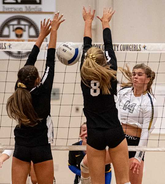 LON AUSTIN/CENTRAL OREGONIAN - Kenna Woodward blasts a kill past a double block from Sisters. Woodward had 10 kills as the Cowgirls defeated the Outlaws in straight sets to win their first match of the season. Crook County is at Madras next Tuesday in a 6 p.m. match.