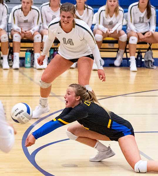 LON AUSTIN/CENTRAL OREGONIAN - Kacie Stafford dives for a ball, while Kenna Woodward looks on. Stafford led the Cowgirls in digs with 24 and aces with five as the Cowgirls defeated the Sisters Outlaws Tuesday night in Prineville.
