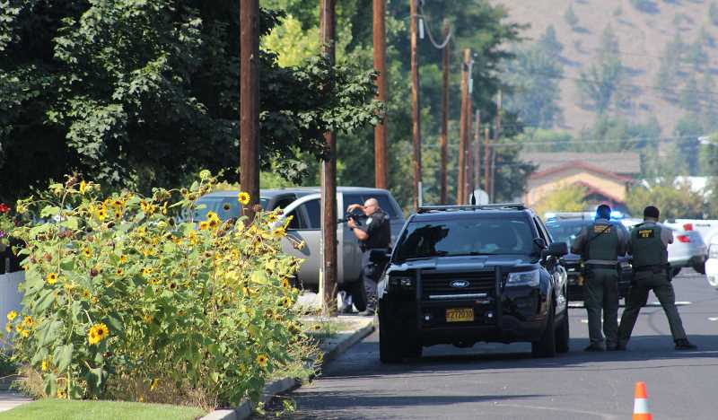 JASON CHANEY/CENTRAL OREGONIAN - Law enforcement officers respond to a threat on East First and Southeast Court on Friday.