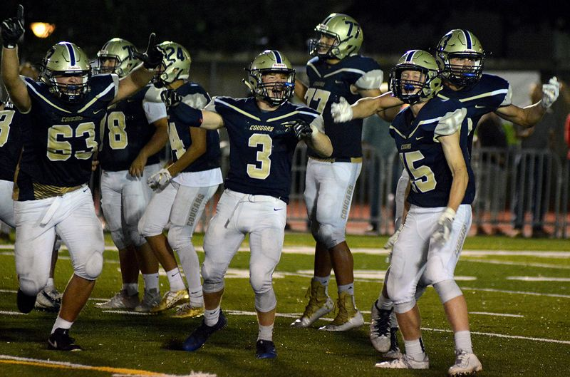 PMG PHOTO: DEREK WILEY - Canby's K'den McMullin (center, no. 3) leads cheers for the Cougars during their 26-22 loss to Lincoln at Canby High School on Friday night.