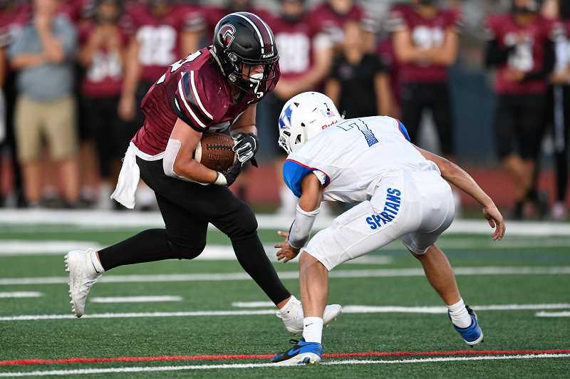 PMG PHOTO: CHRISTOPHER OERTELL - Glencoe's Royce Fasel takes on a Hillsboro tackler during the Tide's game with the Spartans Friday, Sept. 6, at Hare Field.