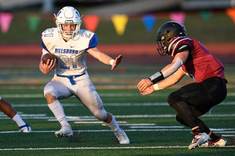 PMG PHOTO: CHRISTOPHER OERTELL - Hillsboro's Thomas Johnson stiff arms a Glencoe defender during the Spartans' game against the Tide Friday, Sept. 6, at Hare Field.