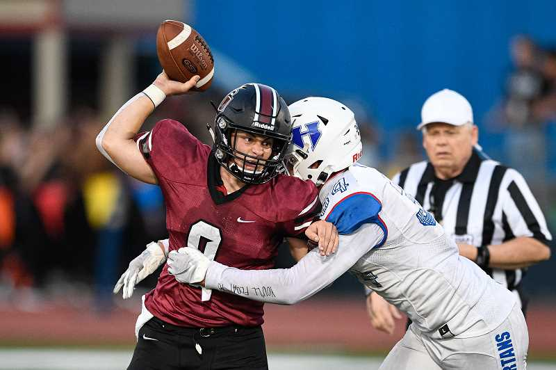 PMG PHOTO: CHRISTOPHER OERTELL - Glencoe quarterback Carson Wilson fights off Hillsboro defender Nate Smith during the Tide's game against the Spartans Friday, Sept. 6, at Hare Field.