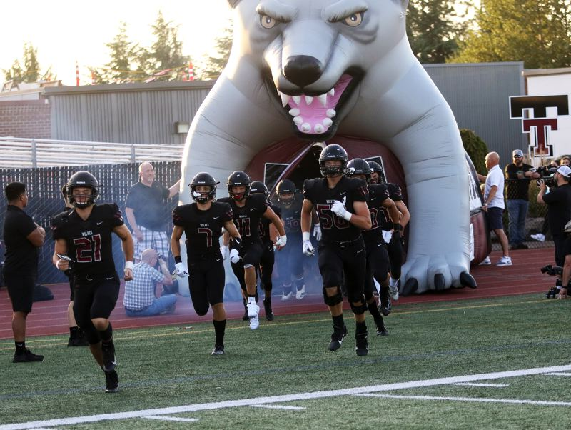 PMG PHOTO: DAN BROOD - Tualatin players take the field prior to Friday's Three Rivers League opener with Lakeridge. The Timberwolves got a 53-7 victory.