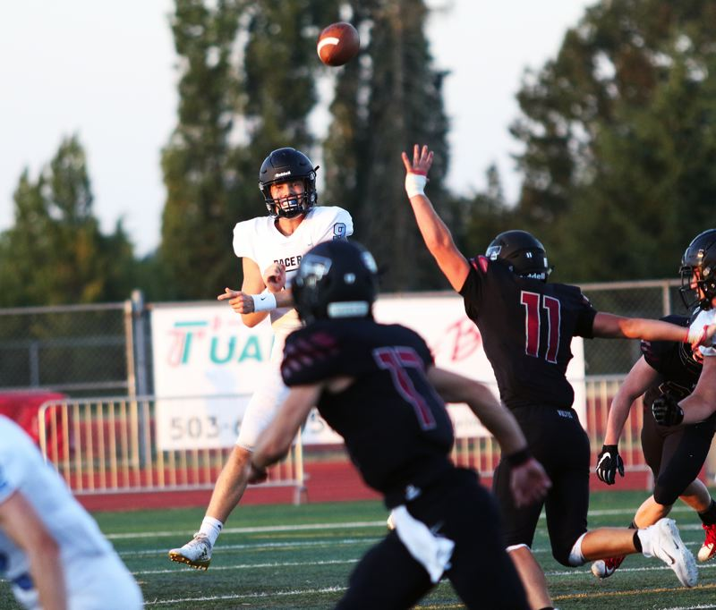 PMG PHOTO: DAN BROOD - Lakeridge senior Cooper Justice throws a pass over the outstretched arms of Tualatin senior Jake Reser (11) during Friday's Three Rivers League contest.