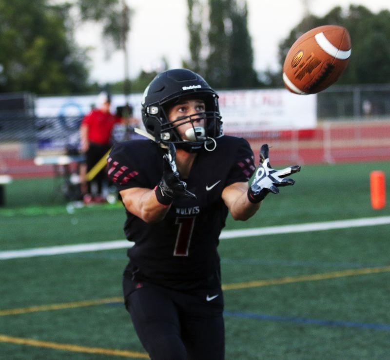 PMG PHOTO: DAN BROOD - Tualatin High School senior Cade McCarty keeps his eyes on the ball as he catches a 31-yard touchdown catch during the Wolves' TRL game with Lakeridge.